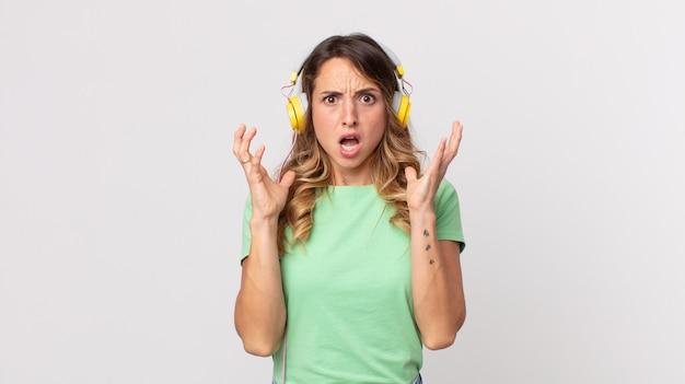 Hübsche dünne frau schreit mit den händen in die luft und hört musik mit kopfhörern