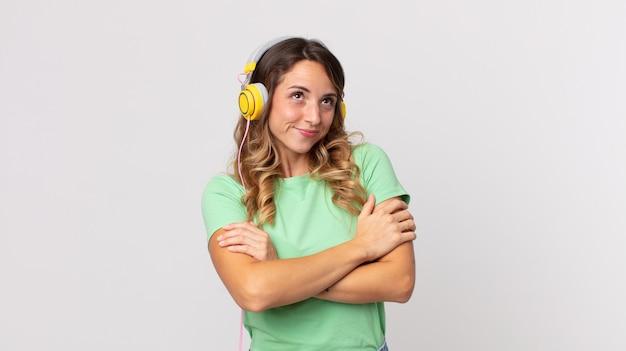 Hübsche dünne frau zuckt mit den schultern, fühlt sich verwirrt und unsicher beim hören von musik mit kopfhörern