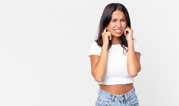 Hübsche dünne hispanische frau, die wütend, gestresst und genervt aussieht und beide ohren bedeckt