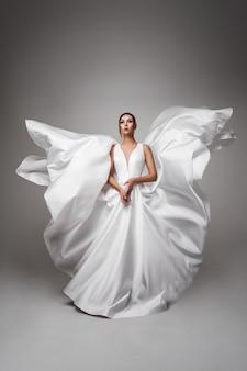 Hübsche dunkelhaarige frau in einem fliegenden hochzeitskleid. weißes kleid flattert im wind. mode hochzeitsfotografie konzept