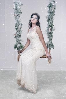 Hübsche eiskönigin auf schaukel zwischen fallendem schnee