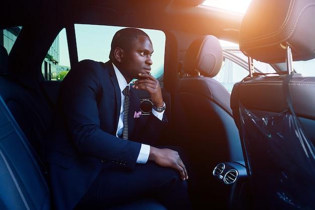 Hübsche, erfolgreiche reiche afroamerikanische geschäftsleute in einem stilvollen schwarzen anzug und krawatte, die in einem luxusauto sitzen. konzept von glück und karrierewachstum