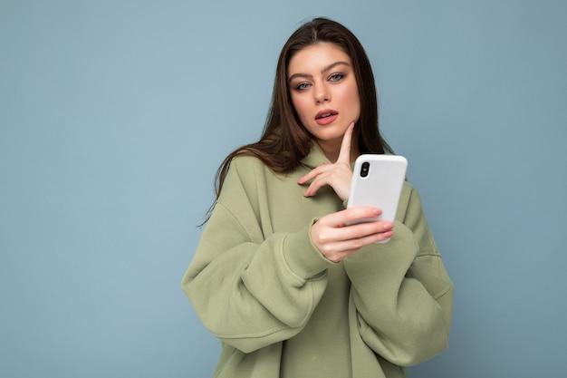 Hübsche erwachsene brünette frau, die einen stylischen grünen hoodie trägt, der mit dem handy sms schreibt, die auf dem hintergrund isoliert ist und in die kamera schaut und denkt. platz kopieren