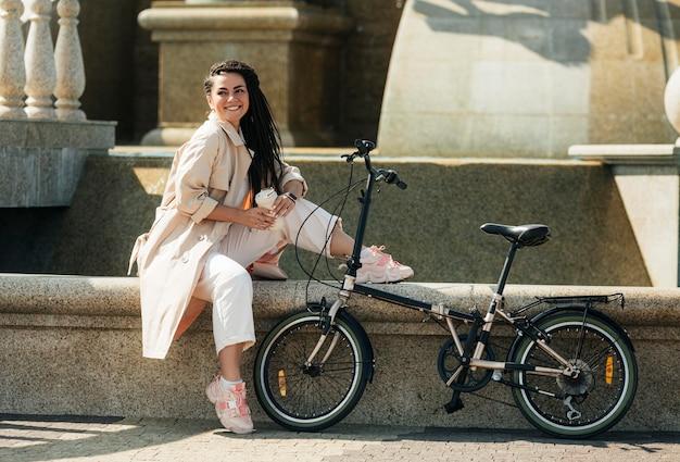 Hübsche erwachsene frau, die mit umweltfreundlichem fahrrad aufwirft