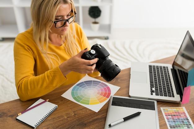 Hübsche erwachsene frau, die professionelle kamera prüft