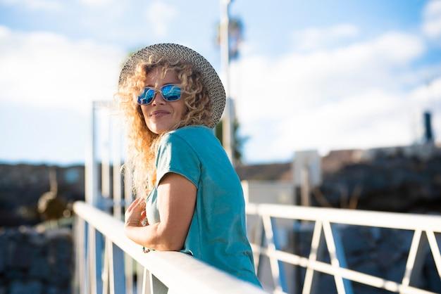 Hübsche erwachsene junge frau lächelt und genießt freizeitaktivität im freien am sonnigen tag