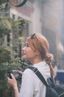Hübsche ethnische frau, die mit kamera reist