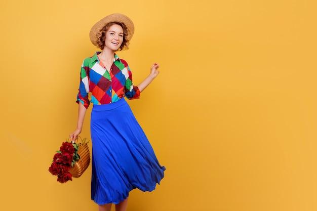 Hübsche europäische frau im blauen kleid, das blumenstrauß über gelbem hintergrund hält. strohhut. sommerstimmung.