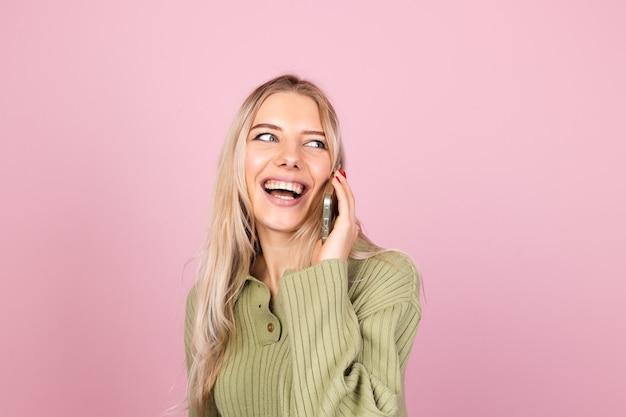 Hübsche europäische frau im lässigen strickpullover auf rosa wand