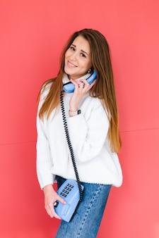 Hübsche europäische frau im lässigen weißen pullover glücklich verspieltes positives halten festnetztelefonlächeln, das gespräch hat