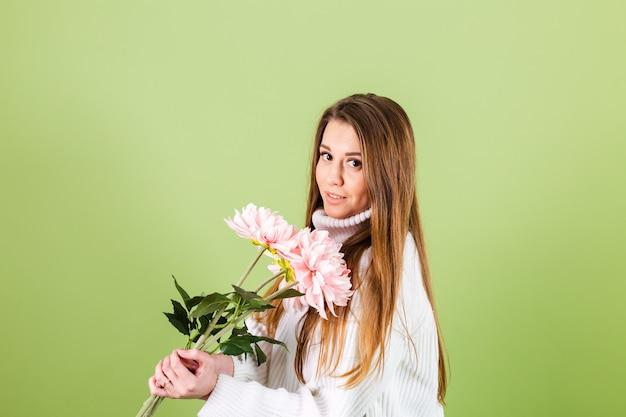 Hübsche europäische frau im lässigen weißen pullover lokalisiert, romantischer blick, der blumenstrauß der rosa blumen mit lächeln hält