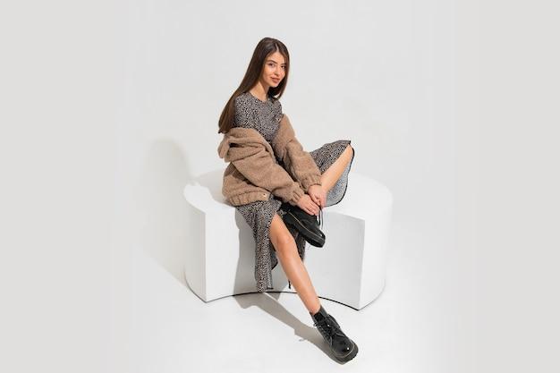 Hübsche europäische frau im winterpelzmantel und im stilvollen kleid sitzen. stiefelette aus schwarzem leder.