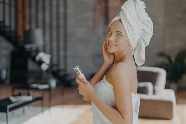Hübsche europäische frau mit gesund strahlender haut minimales make-up hält flasche körperlotion