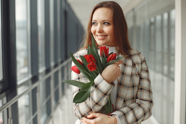 Hübsche europäische frau mit roten tulpen ist in einer hellen modernen halle
