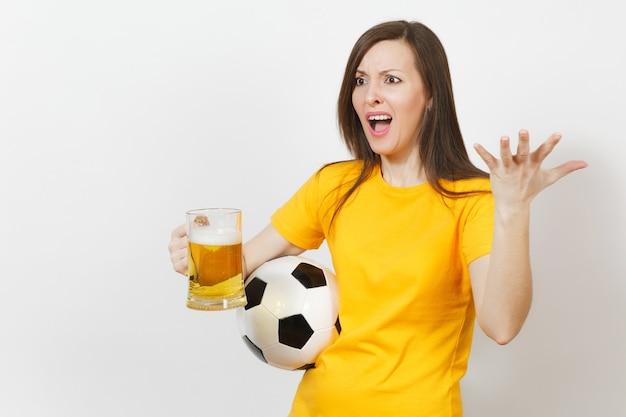 Hübsche europäische junge traurige verärgerte frau, fußballfan oder spieler in gelber uniform hält einen pint-krug bier, sorgt sich um das verlierende team isoliert auf weißem hintergrund. sport, fußball spielen, lifestyle-konzept.