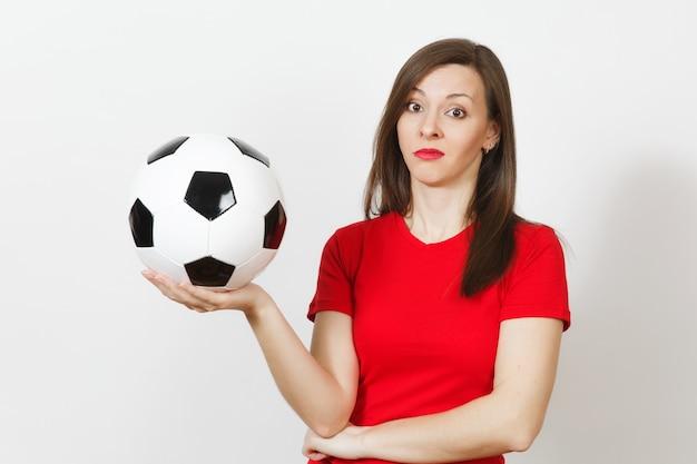 Hübsche europäische junge traurige verärgerte frau, fußballfan oder spieler in roter uniform hält fußball, sorgt sich um das verlierende team isoliert auf weißem hintergrund. sport, fußball spielen, lifestyle-konzept.