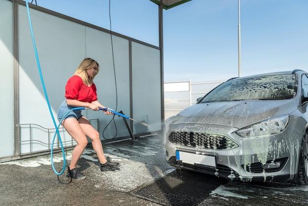 Hübsche fahrerin, die ihr auto mit einem hochdruckschlauch von schmutz befreit, trägt einen reiniger auf das auto auf