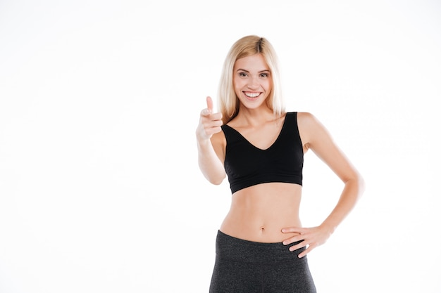 Hübsche fitness-dame, die auf kamera zeigt
