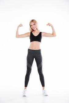 Hübsche fitness-dame, die ihren bizeps zeigt