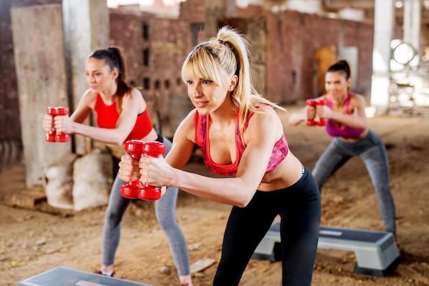Hübsche fitness-mädchen, die schritt-aerobic außerhalb des fitnessraums mit hanteln ausüben.