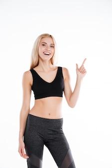 Hübsche fitnessfrau, die auf copyspace zeigt