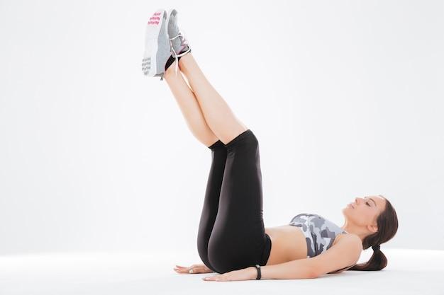 Hübsche fitnessfrau schüttelt presse im studio