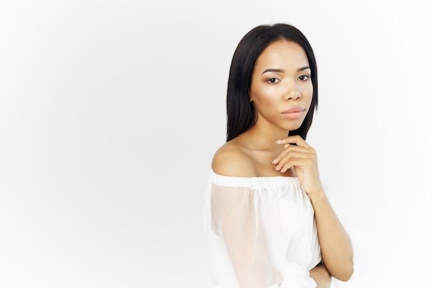 Hübsche frau afrikanische aussehen kosmetik weiße kleider, die hellen hintergrund aufwerfen