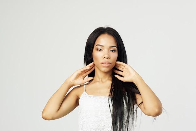 Hübsche frau afrikanisches aussehen weißes tank top make-up frisur mode