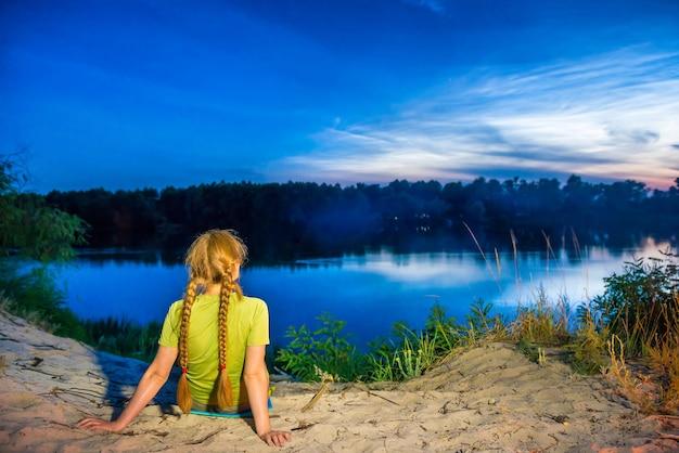 Hübsche frau am strand mit blick auf den sonnenuntergang über dem fluss mit blauem nachthimmel mit sternen