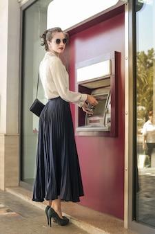 Hübsche frau an einem geldautomaten