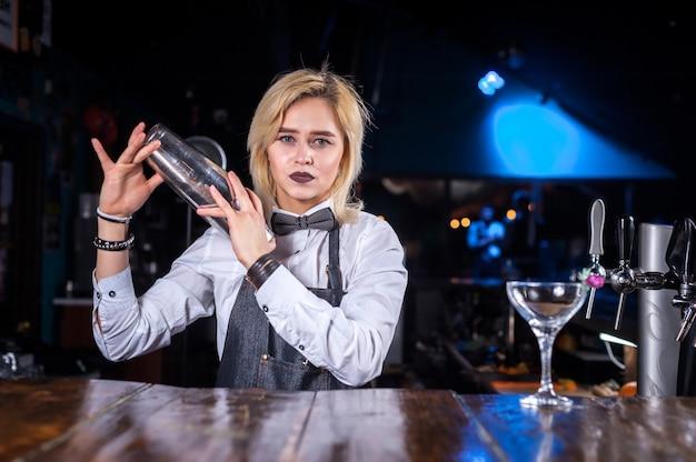 Hübsche frau barkeeper demonstriert seine fähigkeiten über die theke, während sie in der nähe der theke in der kneipe steht