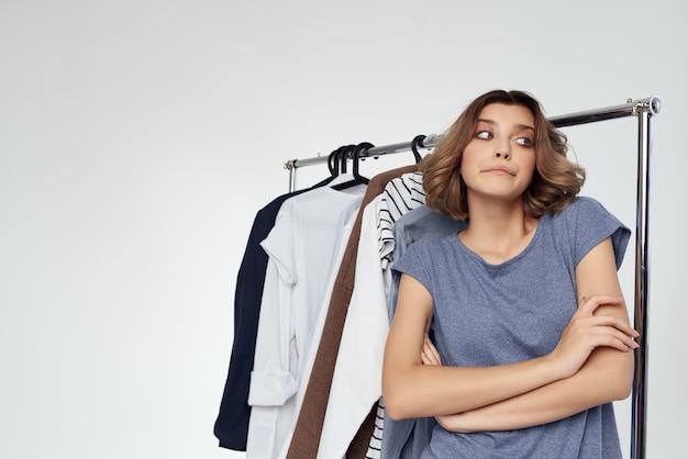 Hübsche frau bekleidungsgeschäft käufer verkauf hellen hintergrund. foto in hoher qualität