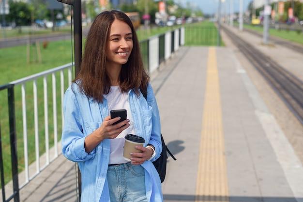 Hübsche frau benutzt smartphone und trinkt morgenkaffee, während sie auf der öffentlichen station auf straßenbahn oder bus wartet.