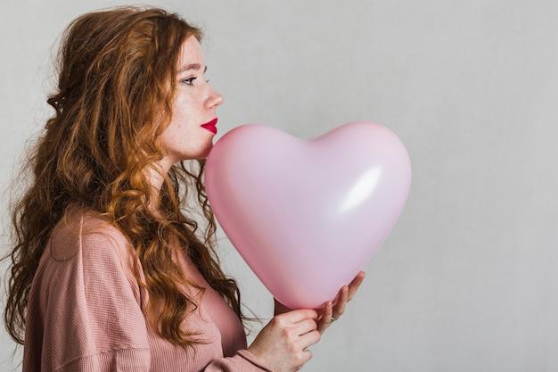Hübsche frau der seitenansicht, die einen ballon hält