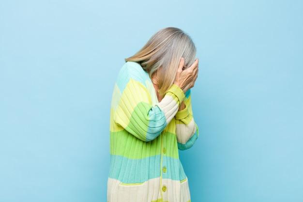 Hübsche frau des älteren oder mittleren alters, die augen mit händen mit einem traurigen, frustrierten ausdruck der verzweiflung, des weinens, der seitenansicht bedeckt