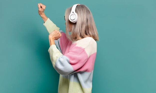 Hübsche frau des grauen haares, das musik mit ihren kopfhörern hört