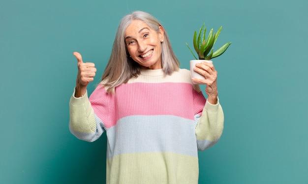 Hübsche frau des grauen haares mit einem kaktus