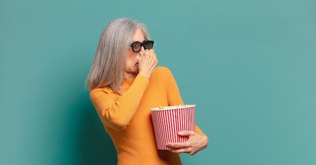 Hübsche frau des grauen haares mit einem popcorn-eimer