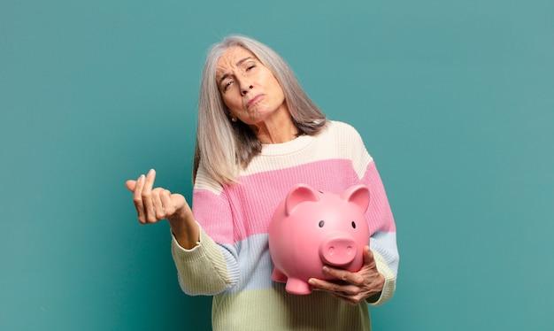 Hübsche frau des grauen haares mit einem sparschwein