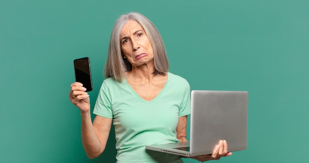 Hübsche frau des grauen haares mit einer zelle und einem laptop