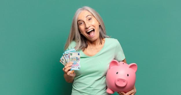 Hübsche frau des grauen haares mit geld und einem sparschwein