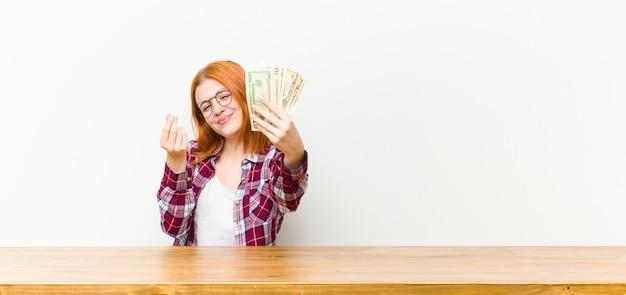 Hübsche frau des jungen roten kopfes vor einem holztisch mit dollarbanknoten