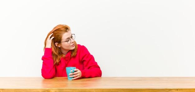 Hübsche frau des jungen roten kopfes vor einem holztisch mit einer kaffeetasse