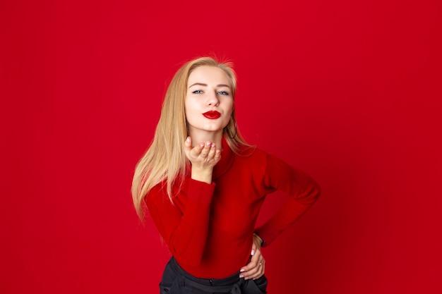 Hübsche frau des portraits sendet luftkuß über rotem hintergrund im studiobild