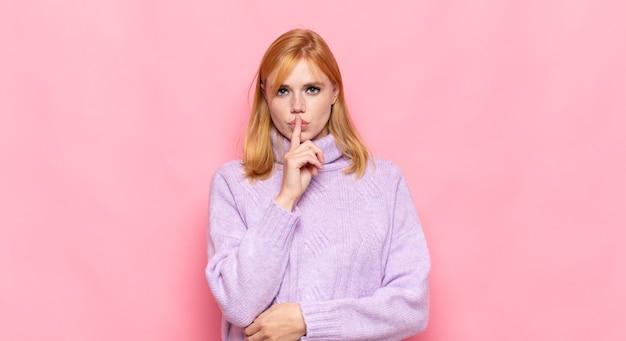 Hübsche frau des roten kopfes, die ernst aussieht und mit dem finger auf die lippen drückt, die stille oder ruhe fordern und ein geheimnis bewahren