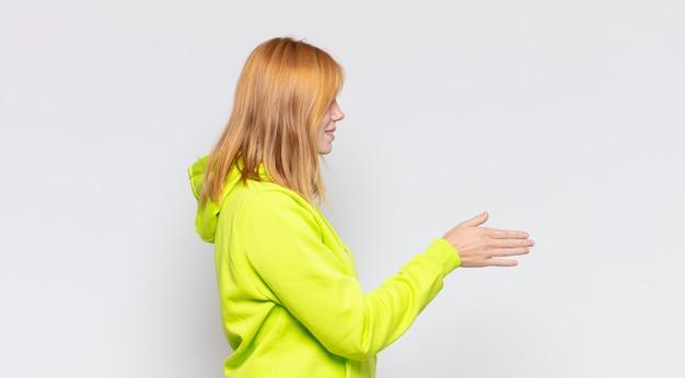 Hübsche frau des roten kopfes, die lächelt, sie begrüßt und einen handschlag anbietet, um einen erfolgreichen deal, kooperationskonzept abzuschließen