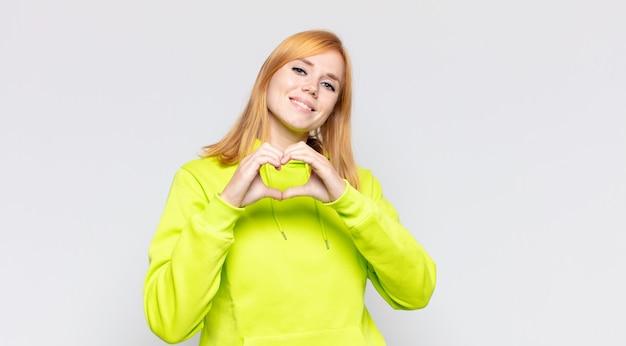 Hübsche frau des roten kopfes, die lächelt und sich glücklich, süß, romantisch und verliebt fühlt und herzform mit beiden händen bildet
