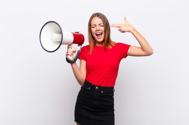 Hübsche frau des roten kopfes, die unglücklich und gestresst aussieht, selbstmordgeste, die waffenzeichen mit der hand macht und mit einem megaphon auf den kopf zeigt
