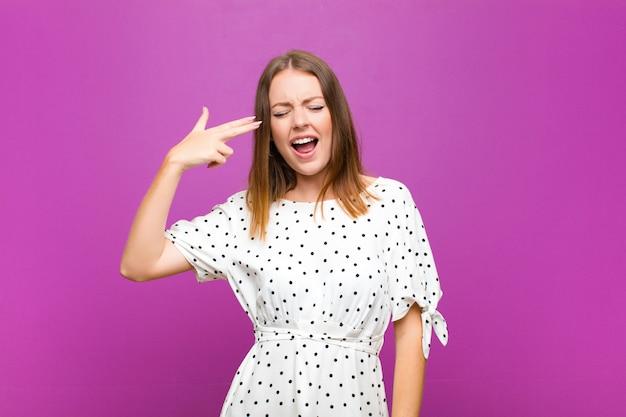 Hübsche frau des roten kopfes, die unglücklich und gestresst aussieht, selbstmordgeste, die waffenzeichen mit der hand macht, zeigt auf kopf gegen lila wand