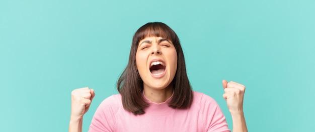 Hübsche frau, die aggressiv mit einem wütenden ausdruck oder mit geballten fäusten schreit, um den erfolg zu feiern